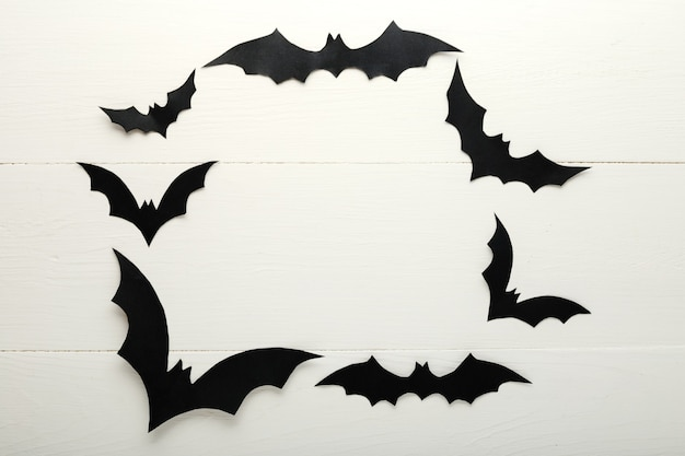 Halloween background with paper bats on white wooden background. frame. halloween holiday decorations. flat lay, top view, copy space. party invitation mockup, celebration.