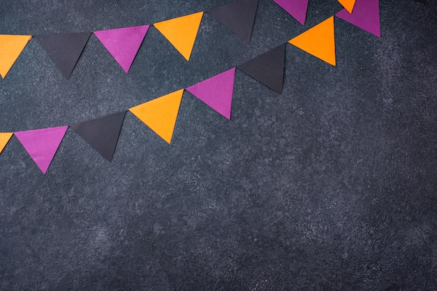 Halloween background with paper garland in black, purple and orange color