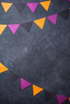 黒、紫、オレンジ色のガーランドとハロウィーンの背景