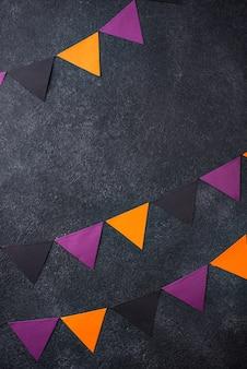 黒、紫、オレンジ色の紙の花輪とハロウィーンの背景