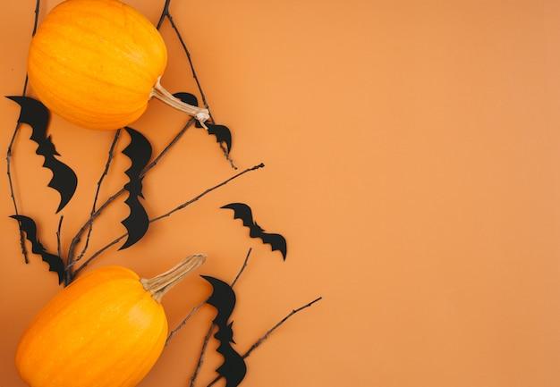 カボチャ、コウモリ、オレンジ色の背景の装飾とハロウィーンの背景。コピースペースを持つハロウィーンパーティー招待状カードモックアップ。