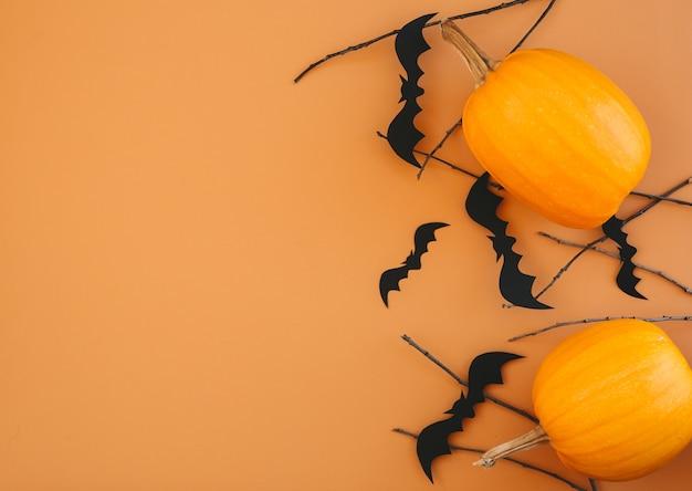 Предпосылка хеллоуина с тыквами, летучими мышами, украшениями на оранжевом фоне. макет пригласительного билета на вечеринку в честь хэллоуина с копией пространства.