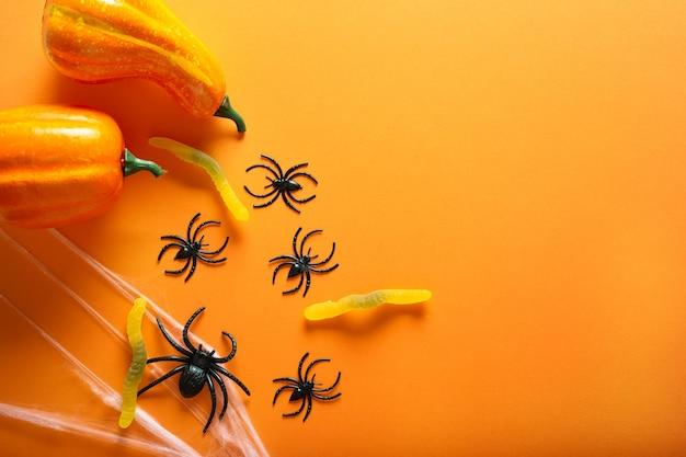 주황색 배경에 할로윈의 상징으로 호박, 사탕 벌레, 거미줄, 거미가 있는 할로윈 배경. 해피 할로윈 개념입니다. 복사 공간이 있는 상위 뷰입니다.
