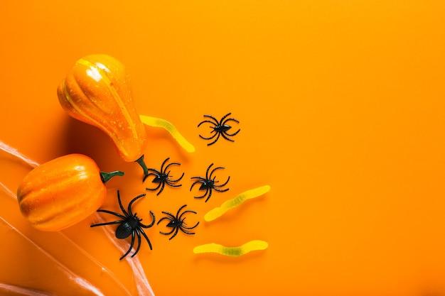 オレンジ色の背景にハロウィーンのシンボルとしてカボチャ、キャンディーワーム、クモの巣、クモとハロウィーンの背景。ハッピーハロウィンのコンセプト。コピースペースのある上面図。
