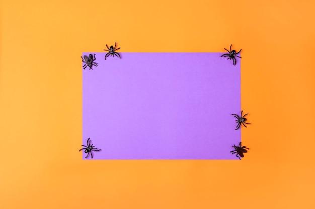 보라색과 주황색 종이와 장난감 거미가 있는 할로윈 배경. 축제 장식 초대 카드입니다.
