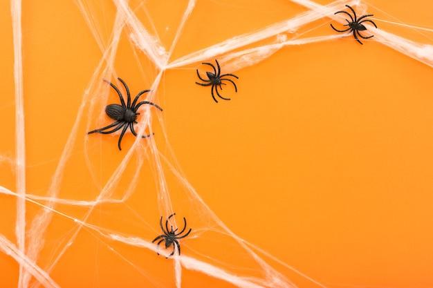 オレンジ色の背景にハロウィーンのシンボルとしてクモの巣とクモとハロウィーンの背景。ハッピーハロウィンのコンセプト。フレーム。スペースをコピーします。