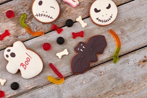 木製の背景のハロウィーンの休日のためのお菓子の恐ろしいクッキーとキャンディーとハロウィーンの背景...