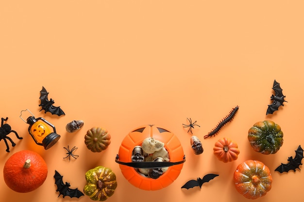 Halloween banner of fun party decorations, candy bowl, pumpkins, sweets, bat, skulls, spooky spider on orange background.