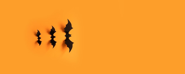 Halloween banner with black bats on an orange surface, top view