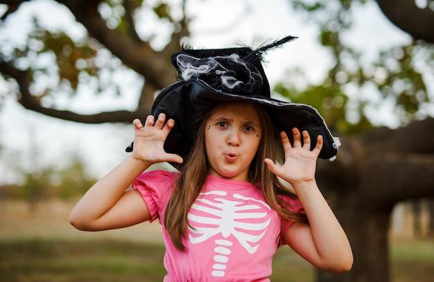 ドレスと黒い帽子のかわいい女の子のハロウィーンの美しい肖像画