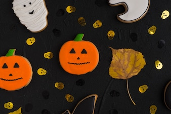 Halloween biscuit and leaf between ornamental skulls