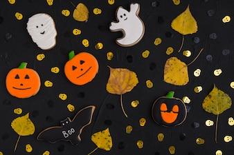 Halloween biscuits and dry leaves between ornamental skulls