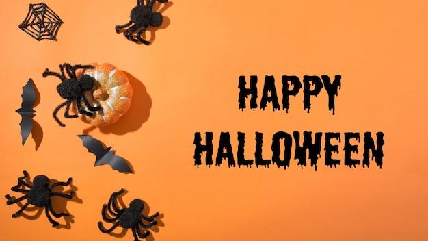 Пустой хэллоуин или приглашение на веселую вечеринку с черными пауками и паутиной на оранжевом фоне. плоский стиль, вид сверху. аксессуары для вечеринок. с праздником хэллоуин - текст.