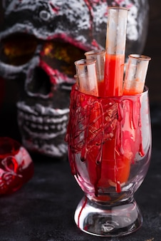 Halloween bloody glass with tomato juice and a human skeleton face as cup on black