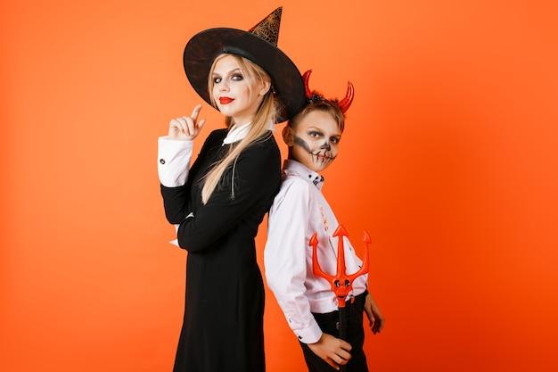 Мальчик и девочка хэллоуина стоят спиной к спине на оранжевом фоне стены. фото высокого качества