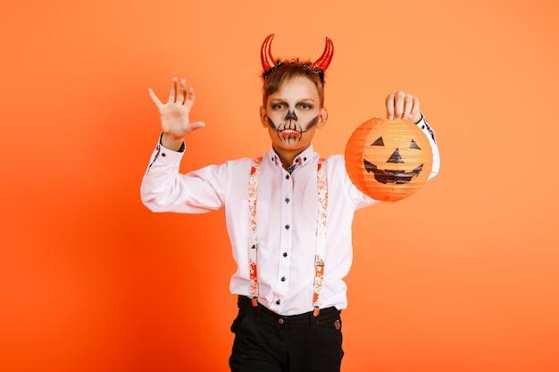 Мальчик-хеллоуин с рогами дьявола делает страшный жест на фоне оранжевой стены. фото высокого качества