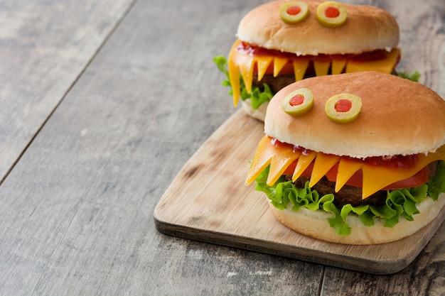 木製のテーブルにハロウィーンのハンバーガーモンスター。コピースペース
