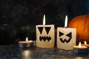 Halloween burning candles standing surrounded by pumpkins