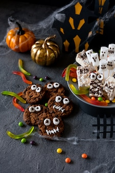 Halloween candy bar funny monsters made of biscuits with chocolate and ghosts marshmallow close-up on the table. halloween party decoration. trick or treat concept.