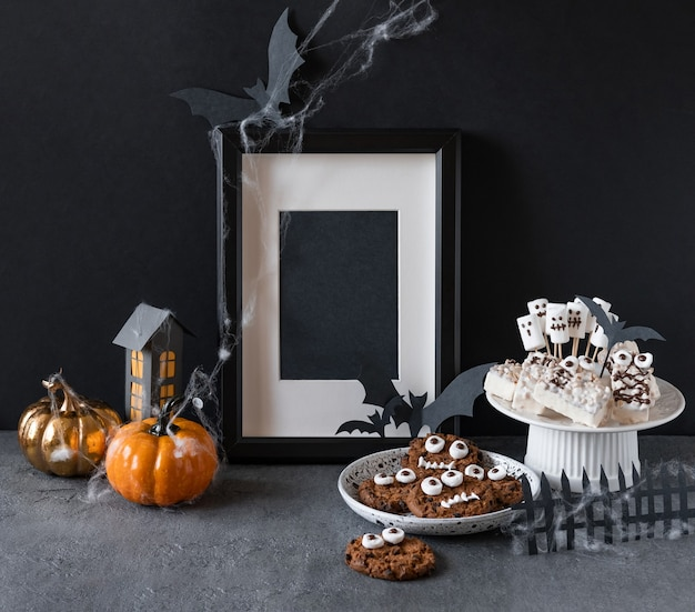 Halloween candy bar: funny monsters made of biscuits with chocolate and ghosts marshmelow close-up on the table