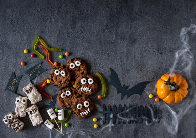 テーブルの上のチョコレートと幽霊マシュマロのクローズアップとビスケットで作られたハロウィーンのキャンディーバー面白いモンスター。ハロウィーンパーティーの装飾。トリックオアトリートのコンセプト。