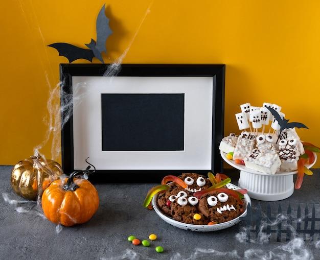 チョコレートとグミのワームとビスケットで作られたハロウィーンのキャンディーバー面白いモンスター、テーブルの上の幽霊マシュマロのクローズアップ。ハロウィーンパーティーの装飾。トリックオアトリートのコンセプト。