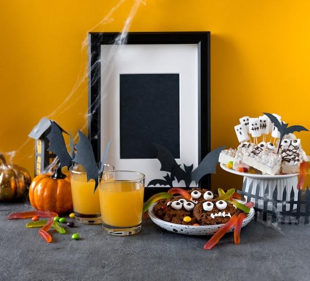 ハロウィーンのキャンディバー:ビスケットとチョコレートとグミのワームで作られた面白いモンスター、テーブルの上の幽霊マーシュメロウのクローズアップ