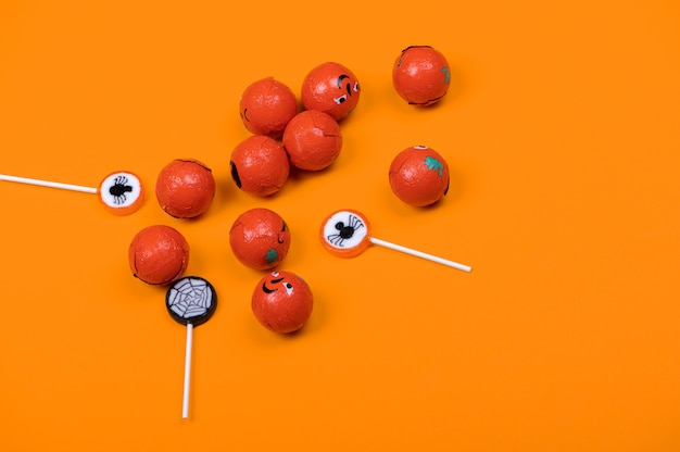 Halloween candy with black spiders,pumpkins and cobweb on orange color background,top view