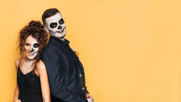 Празднование хэллоуина. студийный снимок молодой пары в праздничных костюмах на хэллоуин и с макияжем на лице. место для вашего текста, рекламы.