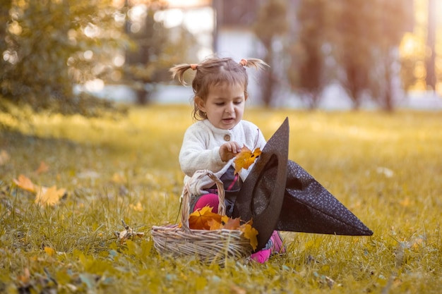 Halloween celebration concept cute little girl lays autumn leaves in witch hat in autumn park