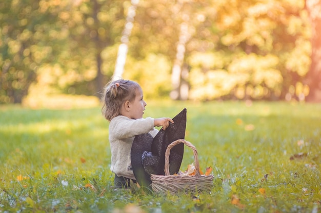 Halloween celebration concept cute toddler playing with witch hat on the lawn in the autumn park on