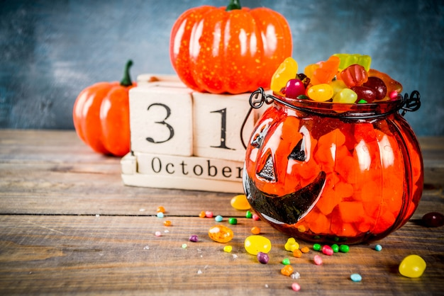 Halloween celebration concept with pumpkin decoration, candy, jack o lantern cup and old retro styled wooden calendar, blue and wooden background,