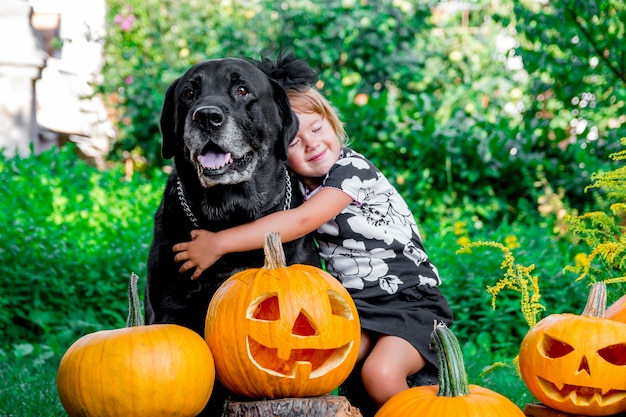 Halloween. child dressed in black near labrador between jack-o-lantern decoration, trick or treat.