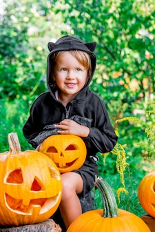 ハロウィン。ジャック・オ・ランタンを手に、トリック・オア・トリートを身に着けた黒服を着た子供。木材、屋外でカボチャを持つ少女。