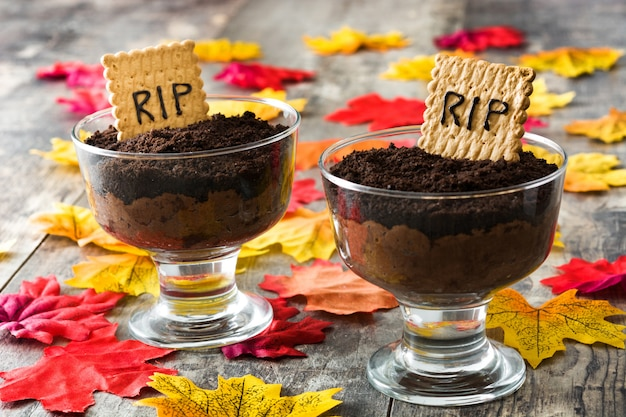 Halloween chocolate mousse with tomb cookie on wooden table