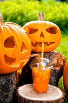 Halloween cocktail near pumpkins decoration on surface