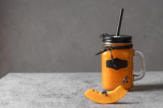 Коктейль на хэллоуин с тыквенным соком, специями, морковным гарниром пауков для праздничной вечеринки на сером