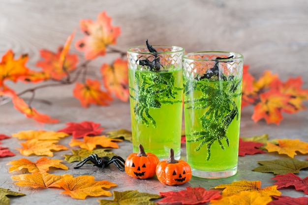 Halloween cocktails. black spiders in glasses with green lemonade, pumpkins and autumn leaves
