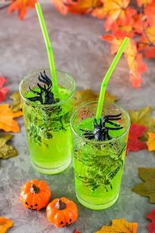 Коктейли на хэллоуин. черные пауки в очках с зеленым лимонадом, тыквами и осенними листьями
