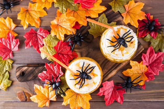 ハロウィーンのカクテル。木製のテーブルの上にグラスにリンゴと氷のかけらとフルーツジュース。