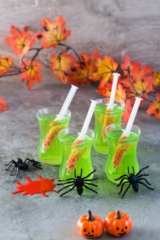 Halloween cocktails. syringes with blood in glasses with green lemonade and spiders on the table.
