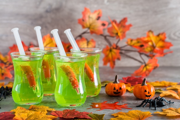 Halloween cocktails. syringes with blood in glasses with green lemonade, spiders