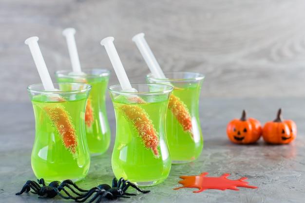 ハロウィーンのカクテル。テーブルの上に緑のレモネードとグラスの血と注射器。
