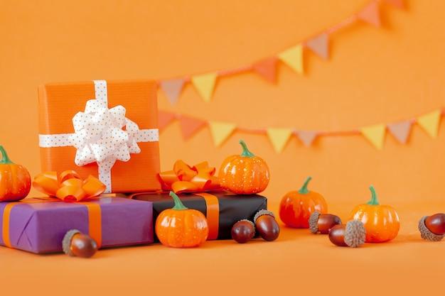 할로윈 화려한 선물 또는 주황색 배경에 호박과 도토리가 있는 선물 상자. 휴일, 생일, 할로윈 파티 축 하 개념입니다.