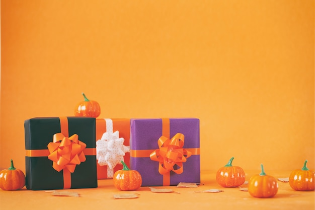 할로윈 화려한 선물 또는 주황색 배경에 호박이 있는 선물 상자. 휴일, 생일, 할로윈 파티 축 하 개념입니다.
