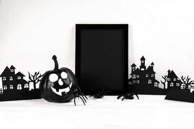 ハロウィーンの組成物。黒のフォトフレームとペーパーアートは村、白のカボチャを放棄しました。