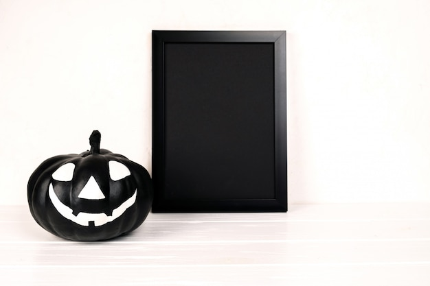 Halloween composition. black photo frame and paper art abandoned village, pumpkin on white.