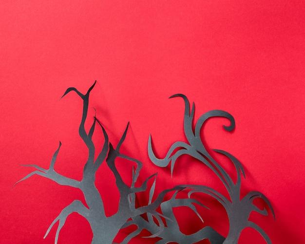Состав хеллоуина бумажных ветвей деревьев ручной работы на красном фоне с пространством для текста. открытка. плоская планировка