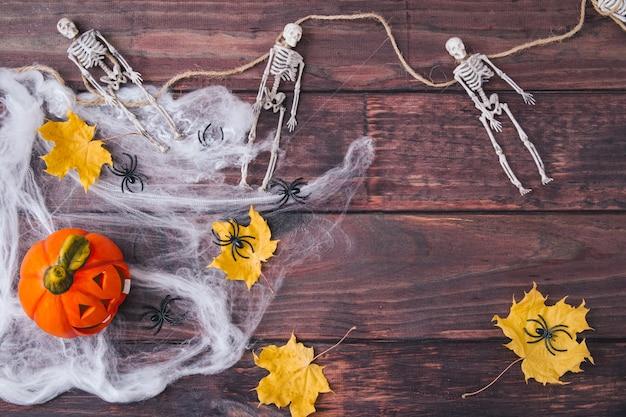 ハロウィーンの作曲。オレンジ色のカボチャ、スケルトン、黄色の乾燥した葉、暗い木製の背景のウェブ上の黒いクモ。