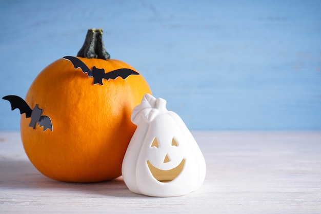 Halloween composition, pumpkins and bats on wooden background, place for text.